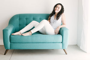 barefoot woman relaxing on a teal couch