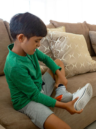 boy sitting on a couch removing his shoe