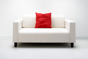 white love seat with red pillow