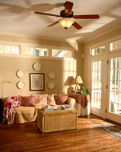 sunroom couch with ceiling fan, wicker ottoman, and hardwood floor